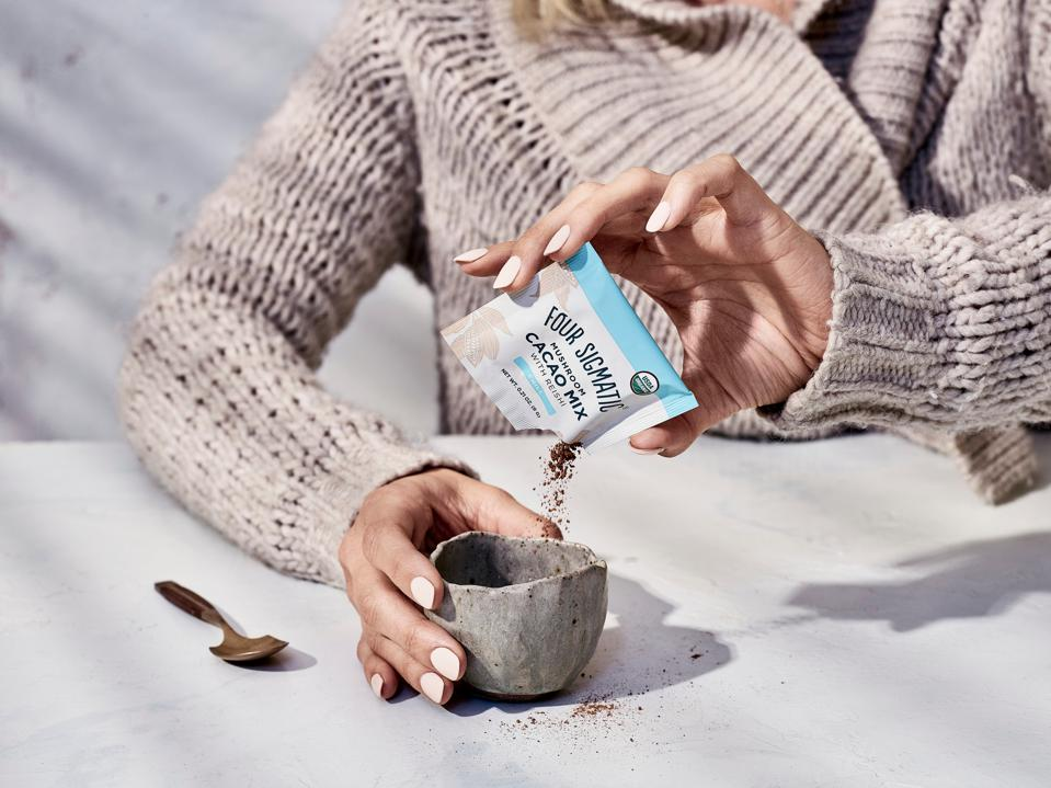 A woman pours Foursigmatic Cacao Mix into a cup.