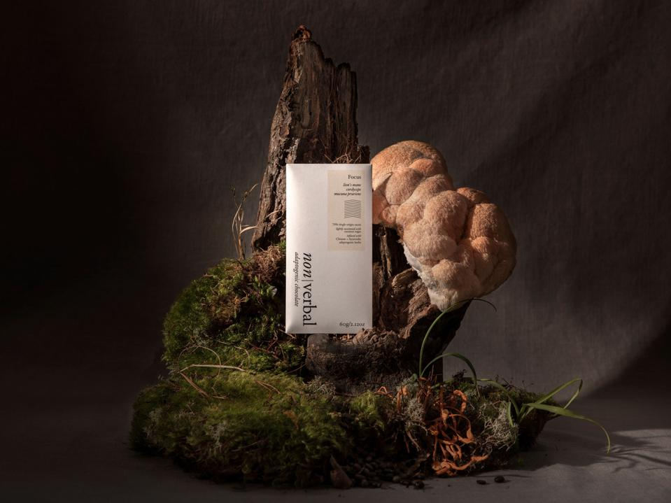 A Non Verbal chocolate bars on a wood mushroom display.
