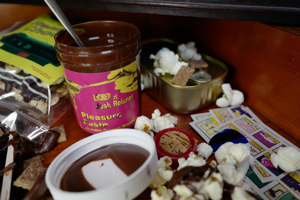 An open jar of Licked Pleasure Paste on a table with popcorn and snacks.