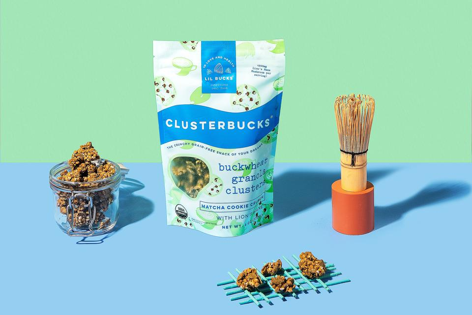 A bag of Lil Bucks Matcha Cookie Crunch Clusterbucks next to a jar of granola.