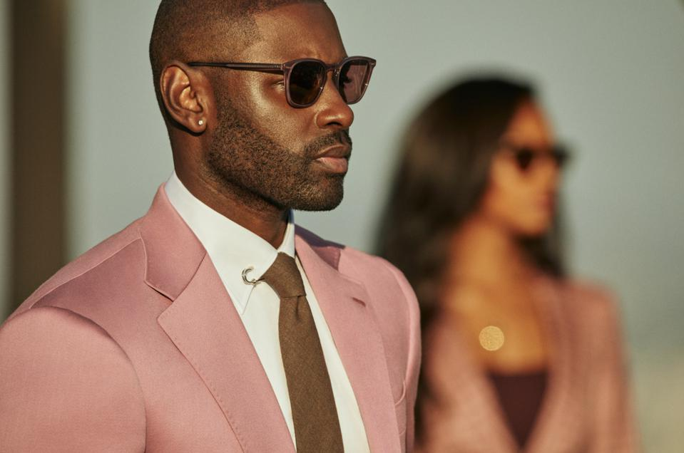 a male and a female model wearing sunglasses and pink matching suits