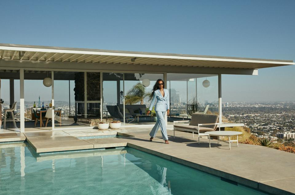 a female model wearing blue suit and sunglasses by a hill top pool