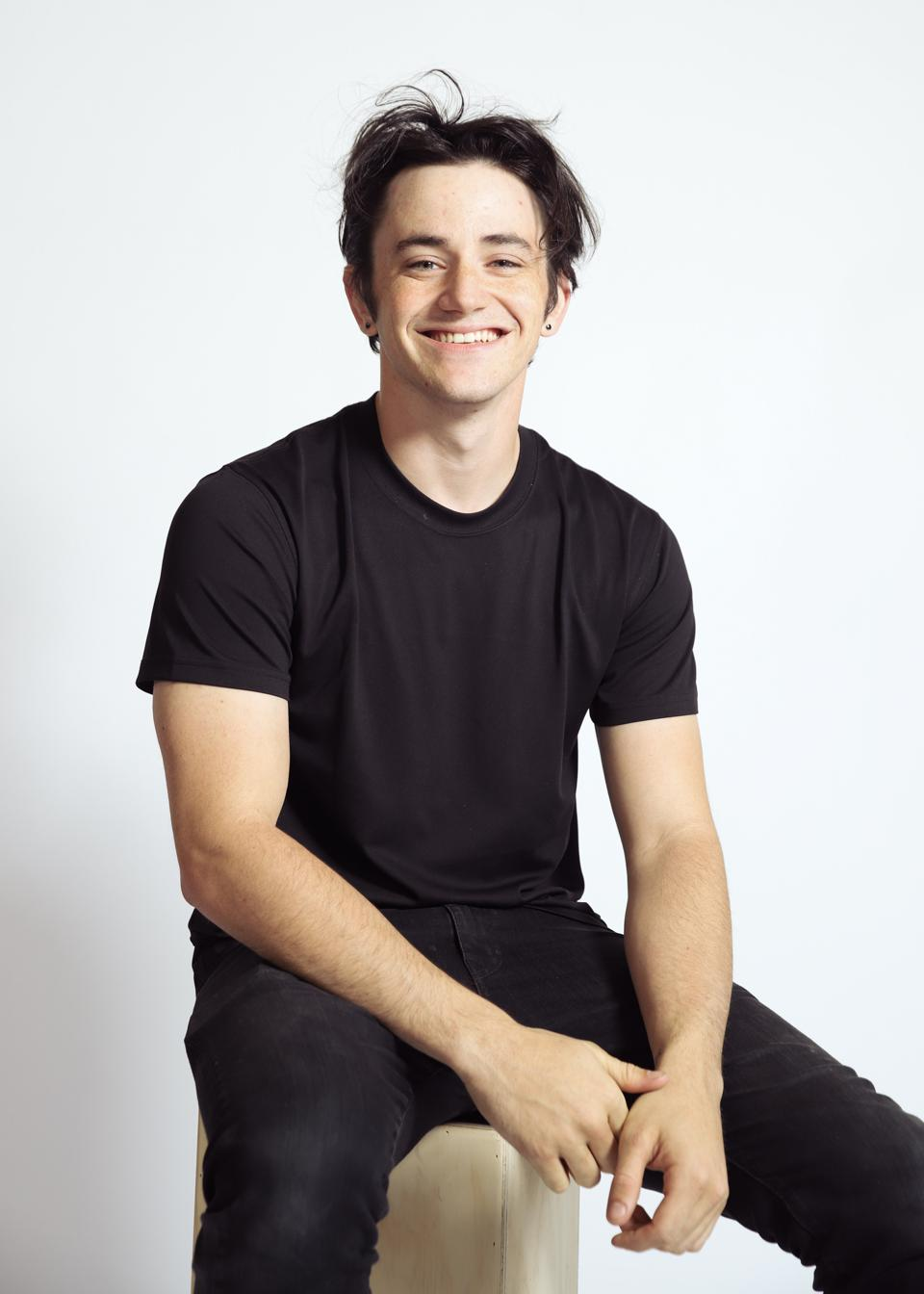 Handsome male sitting on a pillar with a white background. Black outfit.