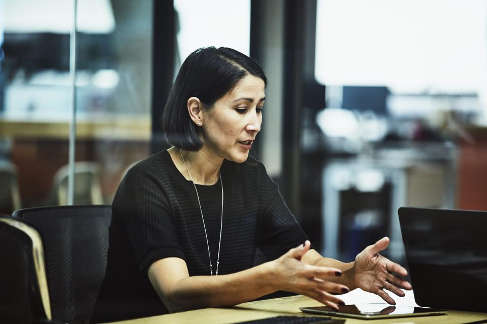 Businesswoman explaining data on digital tablet during meeting in office conference room