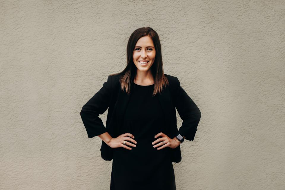 Gaby Cavins, executive director of Employee Success at Villyge, smiling with hands on hips.