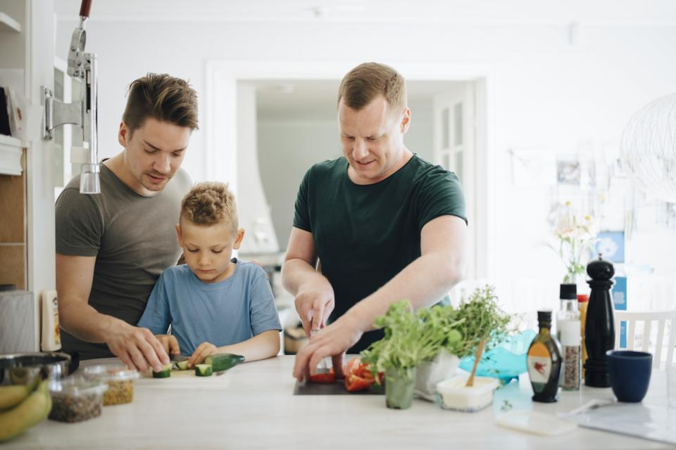Homosexual fathers and son cutting cucumber in kitchen