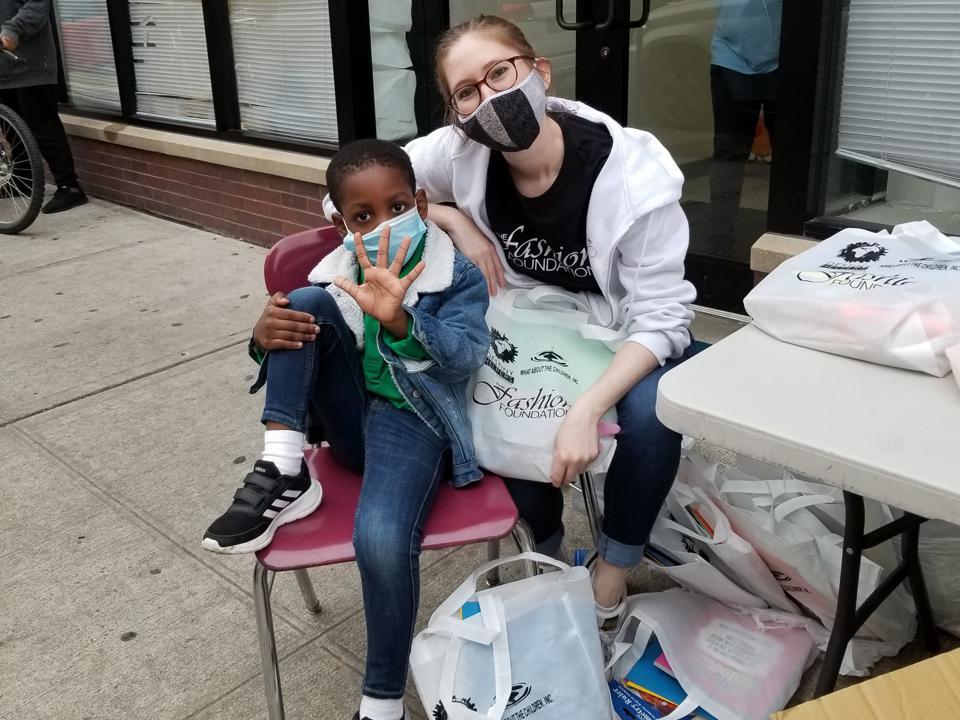 Amanda Munz sits with a young boy, in masks, surrounded by The Fashion Foundation bags.