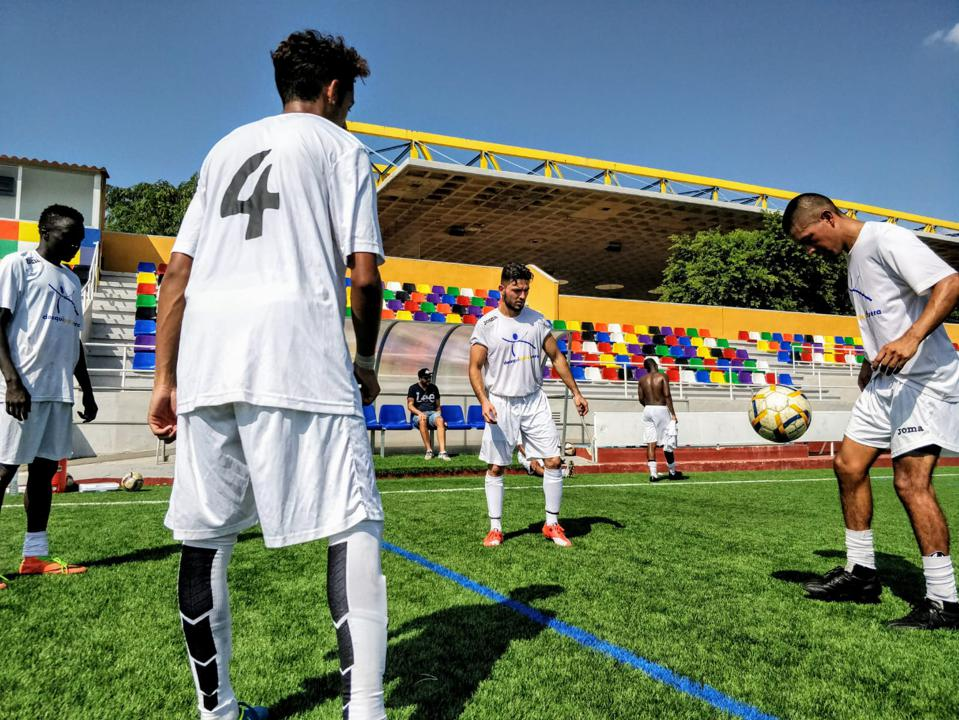 Players at Alicante City FC warm up with the ball at the academy's training complex.