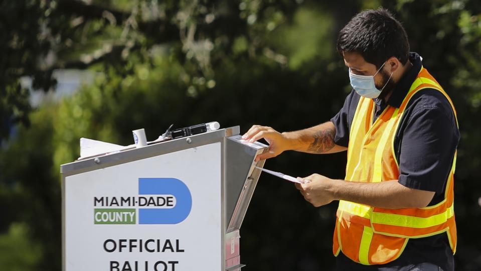 Florida election worker puts ballot in ballot drop box
