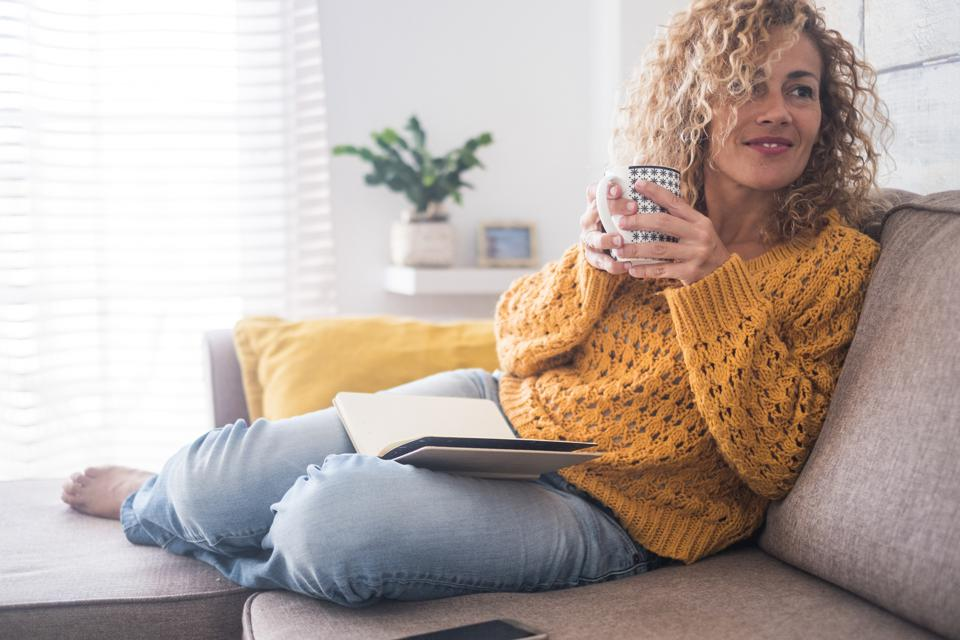 Beautiful 40 years old caucasian lady sit down on the sofa drinking tea and reading a book for afternoon indoor leisure activity at home - after work lifestyle for people concept