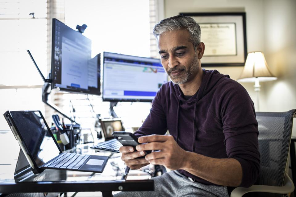 Man working in home office reviewing financial data on smartphone