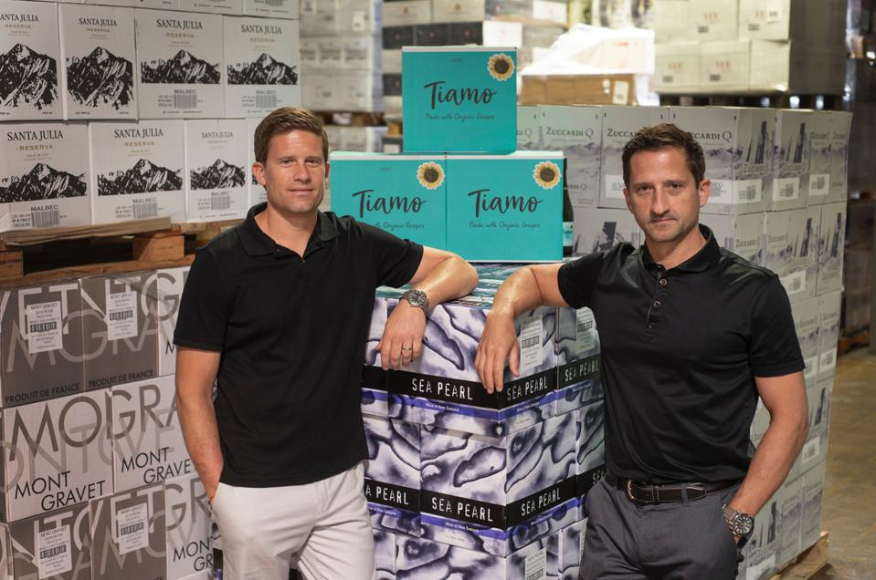 Brothers Jordan (L) and Adam Sager, the founders of Kind of Wild wines with boxes of wine.