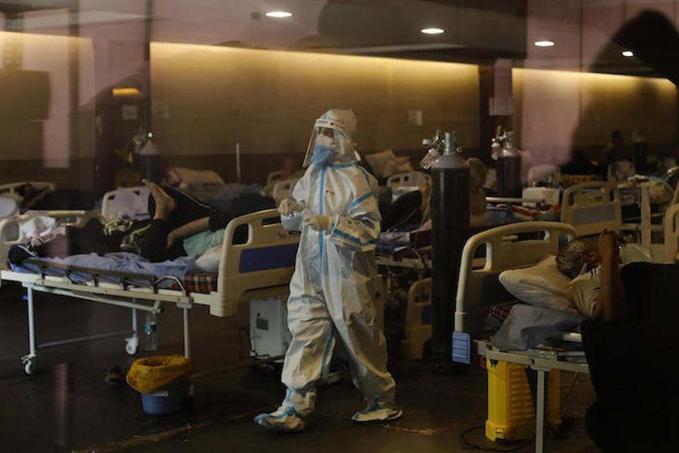 On May 2, 2021, a health worker wearing PPE tends to patients in a banquet hall temporarily converted into a COVID-19 emergency ward in New Delhi, India.