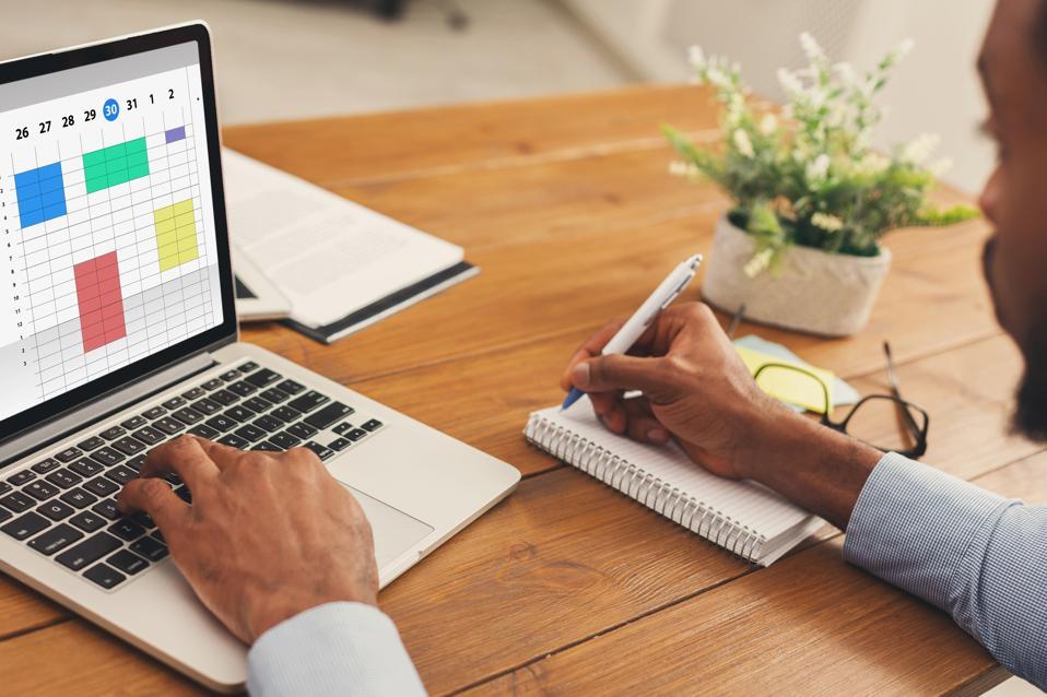 Businessman using online planner to organize work agenda.