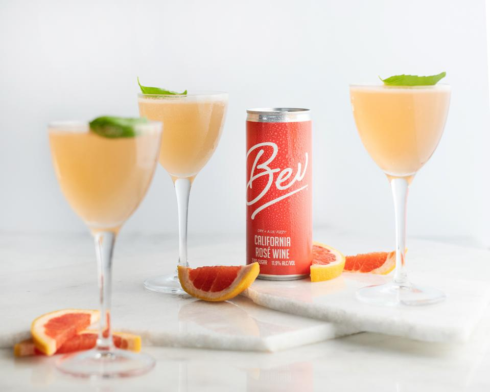 A can of Bev wine sits among three glasses and grapefruit wedges.