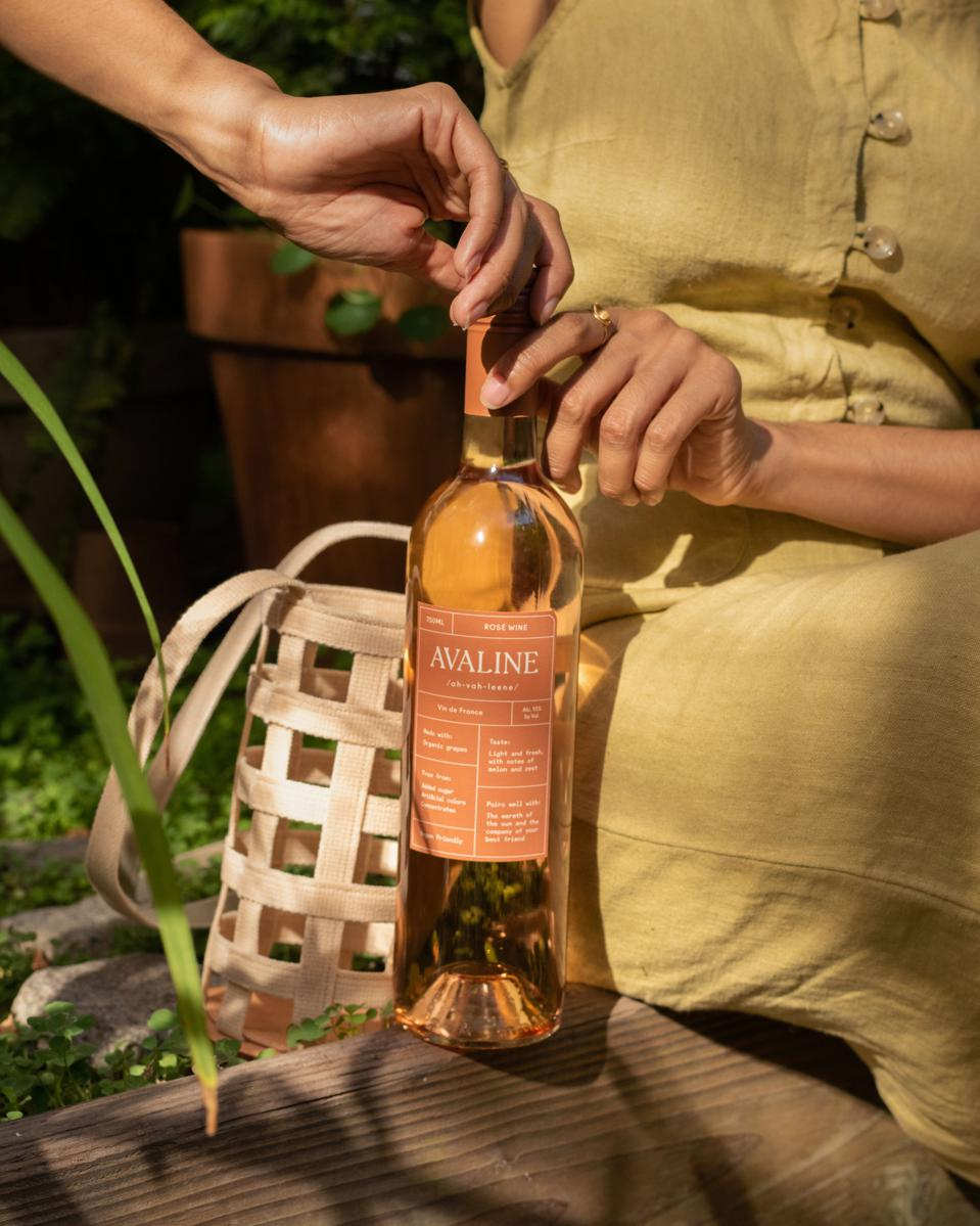 A woman is opening a bottle of Avaline rosé with her purse in the background.
