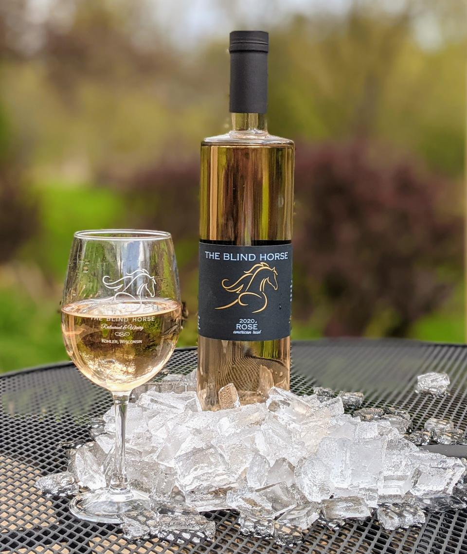 A bottle of rosé and a glass sit on a picnic table with ice.