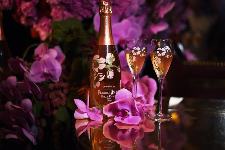 A bottle of Perrier-Jouët Belle Epoque rosé sits on a table with matching floral glasses and flowers.