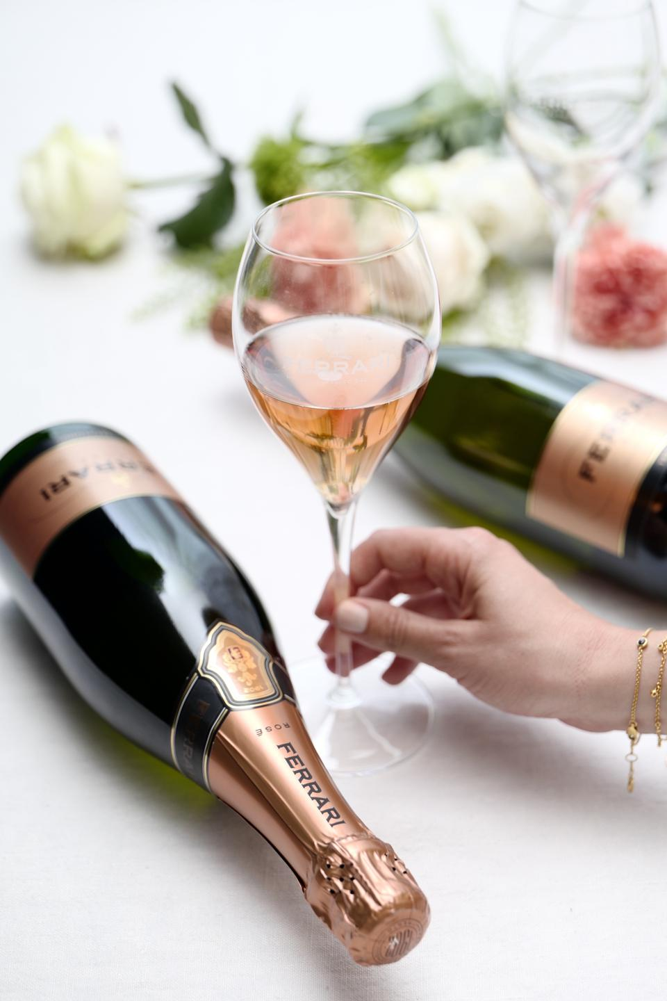 A woman holds a glass of Ferrari Trento sparkling rosé in between two bottles.