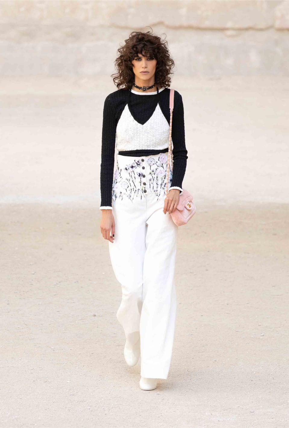 Mica Arganaraz is wearing a cotton palazzo trousers with a leafy wildflowers embroidered with beaded stems and sequins petals bloom around the waist, representing the flowers of Provence, paired with a two-tone top and sweater