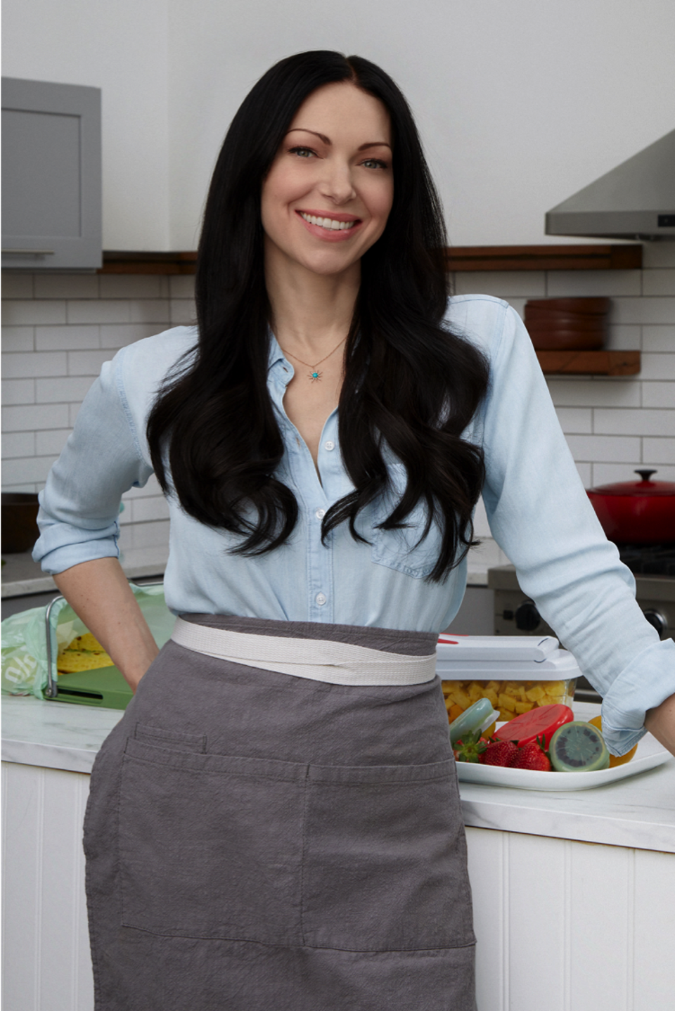 Laura Prepon posing in a kitchen with her PrepOn Kitchen cookware line