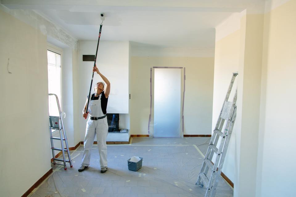 Craftswoman painting home interior