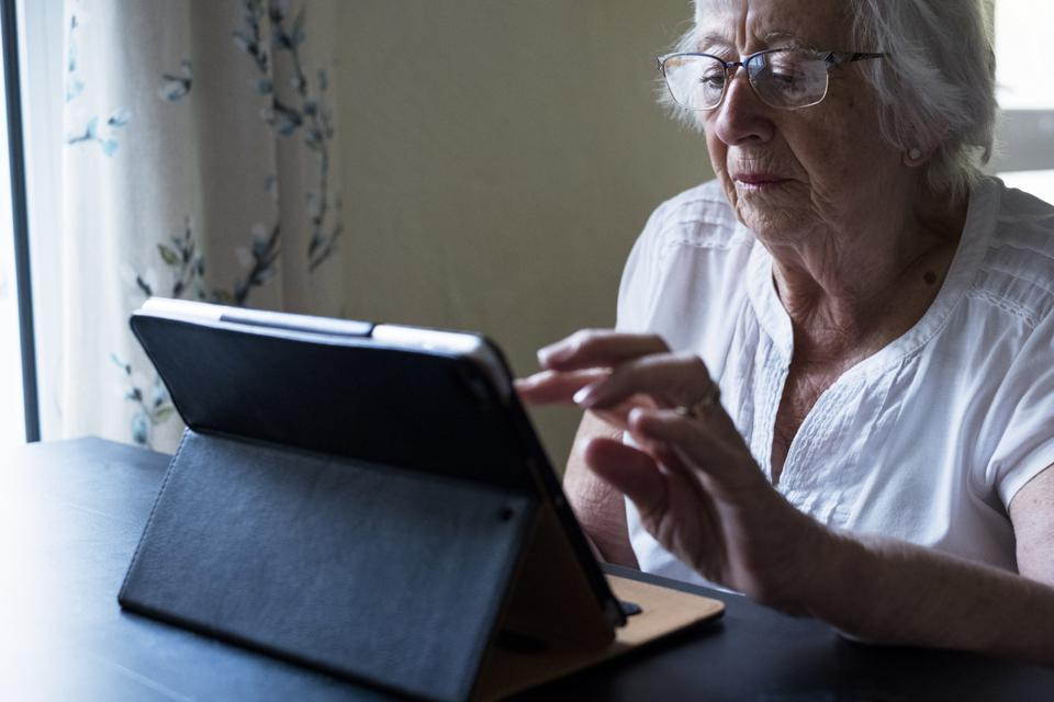 Close up of senior woman sitting at a table, using a digital tablet, using the touch screen.