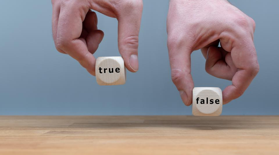 True or False? Two Hands hold two dice with the words ″TRUE″ and ″FALSE″. The dice with the label ″TRUE″ is chosen.