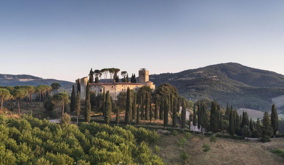 Un forte in pietra ai piedi circondato da verdi colline.