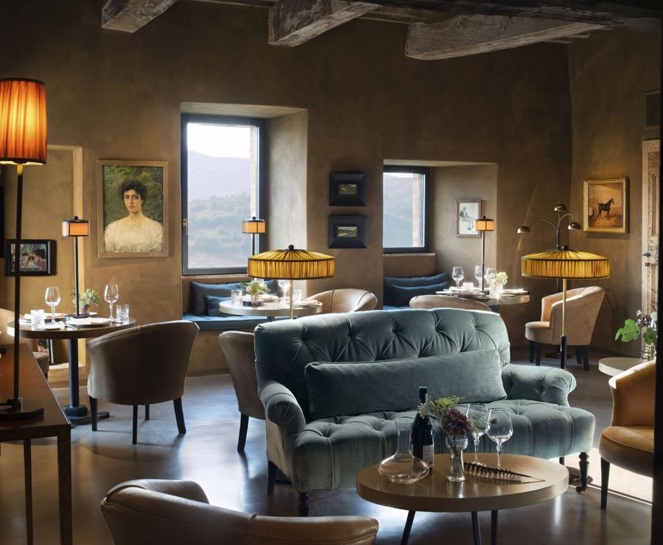 Un ristorante all'interno di muri in pietra con dipinti ad olio e divani imbottiti Sky Blue