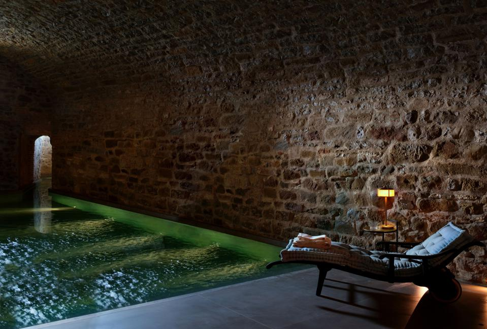 Una piscina con luci verdi all'interno di un'antica cantina