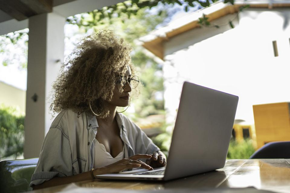 Mid adult woman using laptop at home