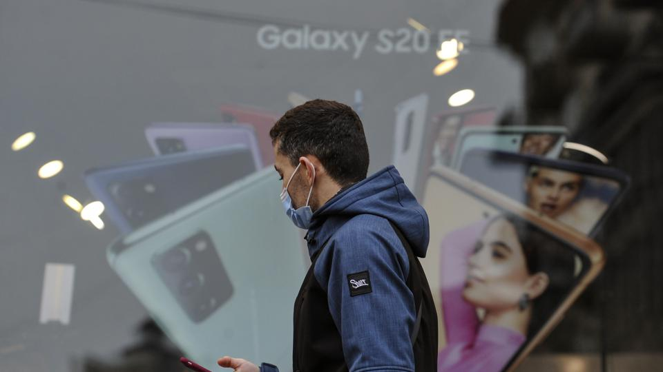 Un uomo che indossa una maschera mentre usa uno smartphone cammina ...