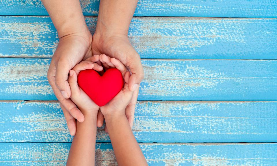 Red heart in child and mother hands on old blue wooden table showing importance of happiness in motherhood.