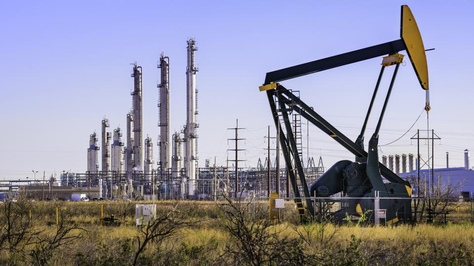 Pumpjack (oil derrick) and refinery plant in West Texas