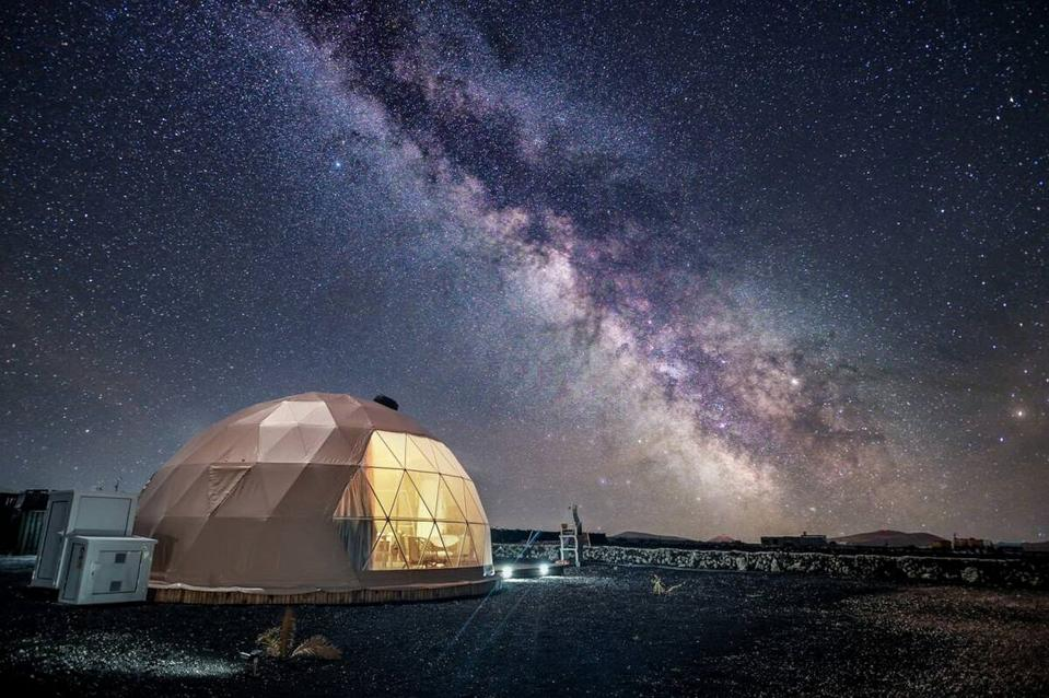 A sky full of stars illuminates the night over an eco glamping dome in the Canary Islands