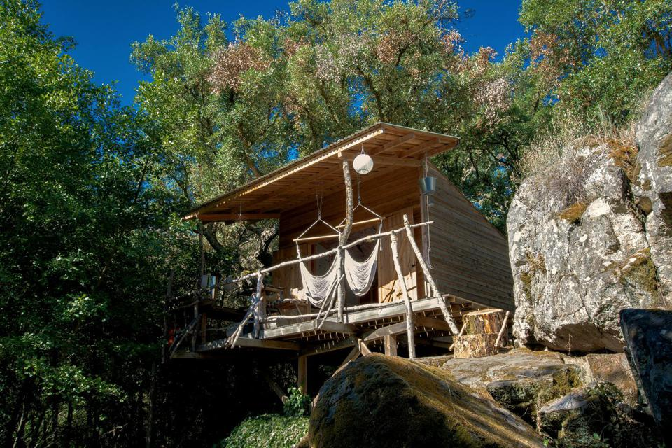 The wooden glamping cabin in Portugal is perched on a hillside above a river