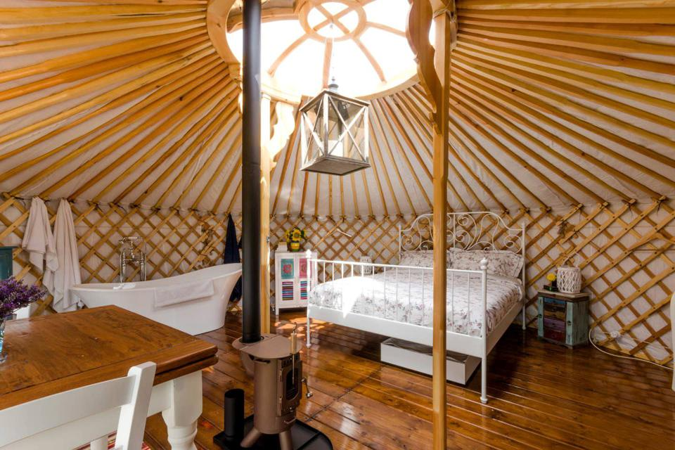 The luxury yurt in Italy is large and well furnished with a big bed and a bathtub