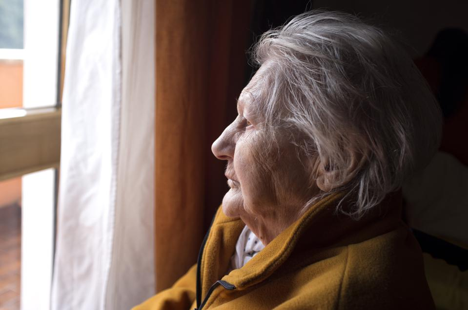Woman with gray hair shown in profile looking out a window