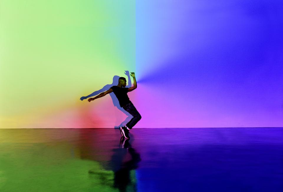 Man Dancing in abstract space with lots of colours around him