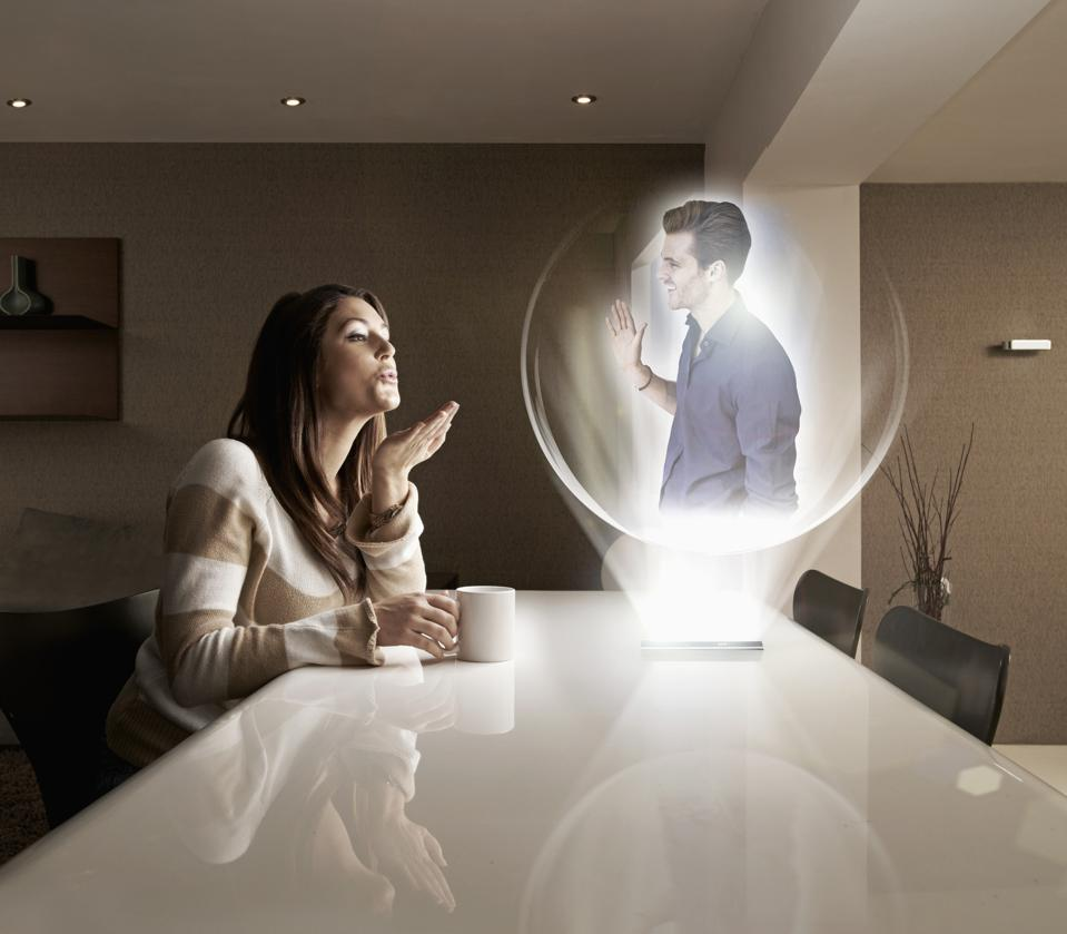 Man and woman having a video call using futuristic 3D device