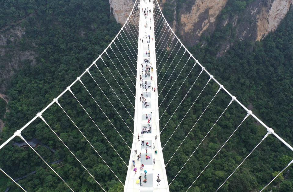 Aerial view of tourists walking on the glass-bottomed bridge at the Zhangjiajie Grand Canyon