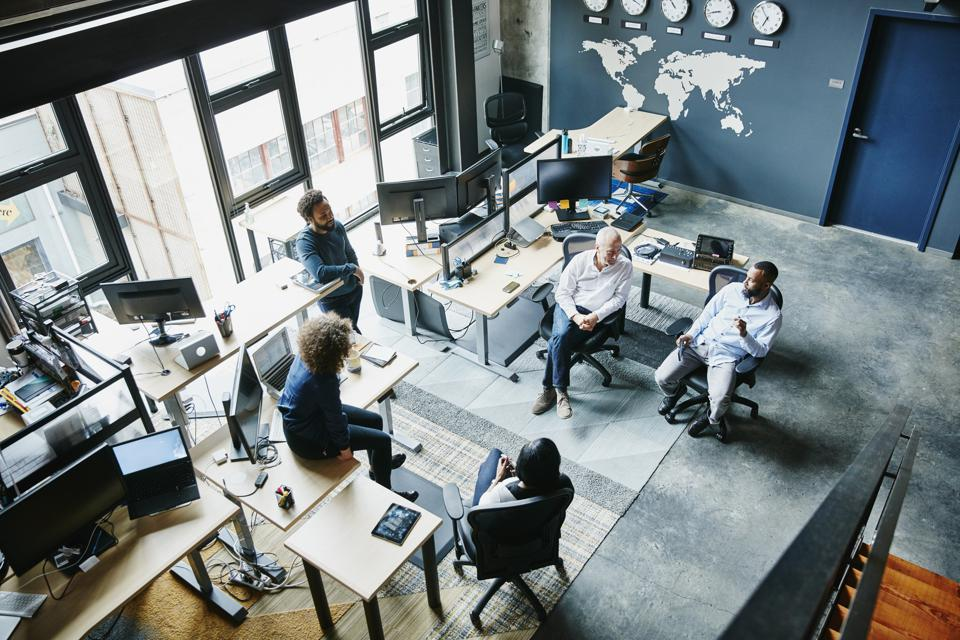 Coworkers having informal project meeting in high tech office overhead view