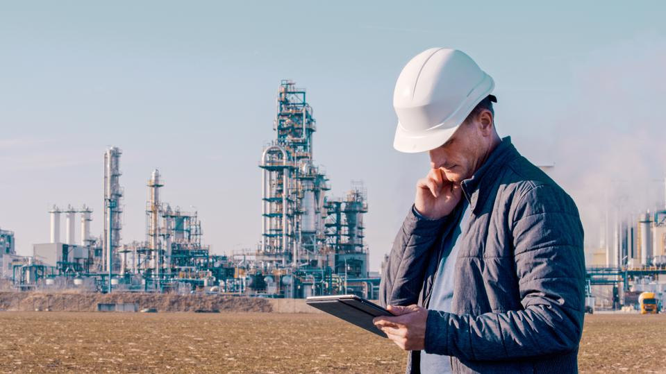 Engineer using tablet near oil refinery.