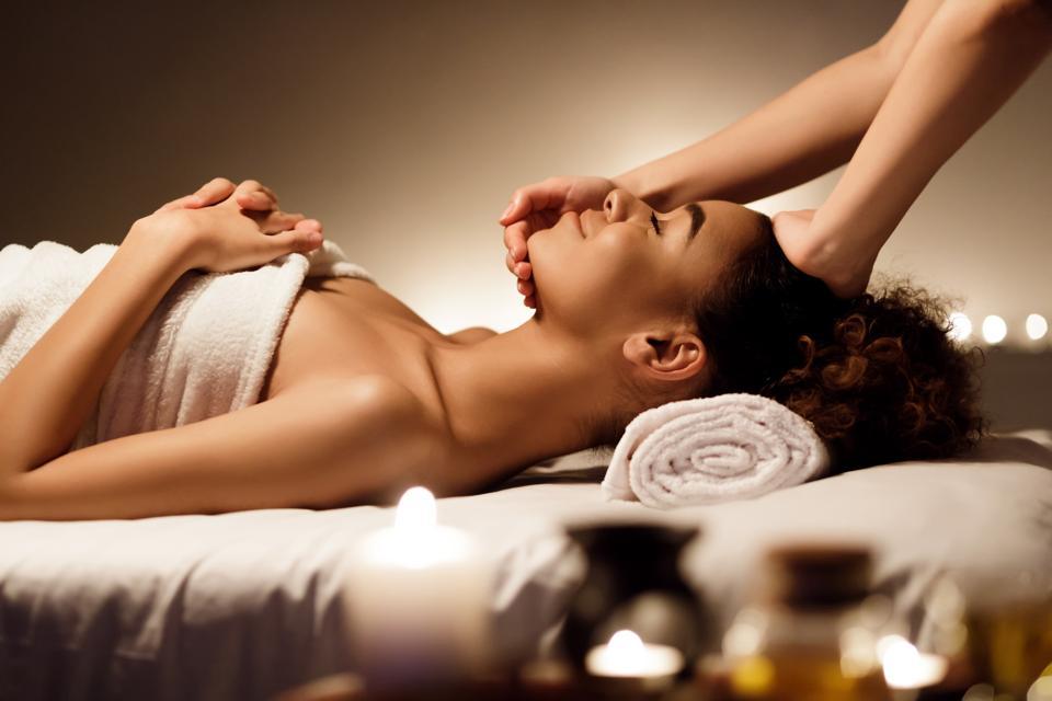 Tratamiento de spa. Mujer afro disfrutando de un masaje facial