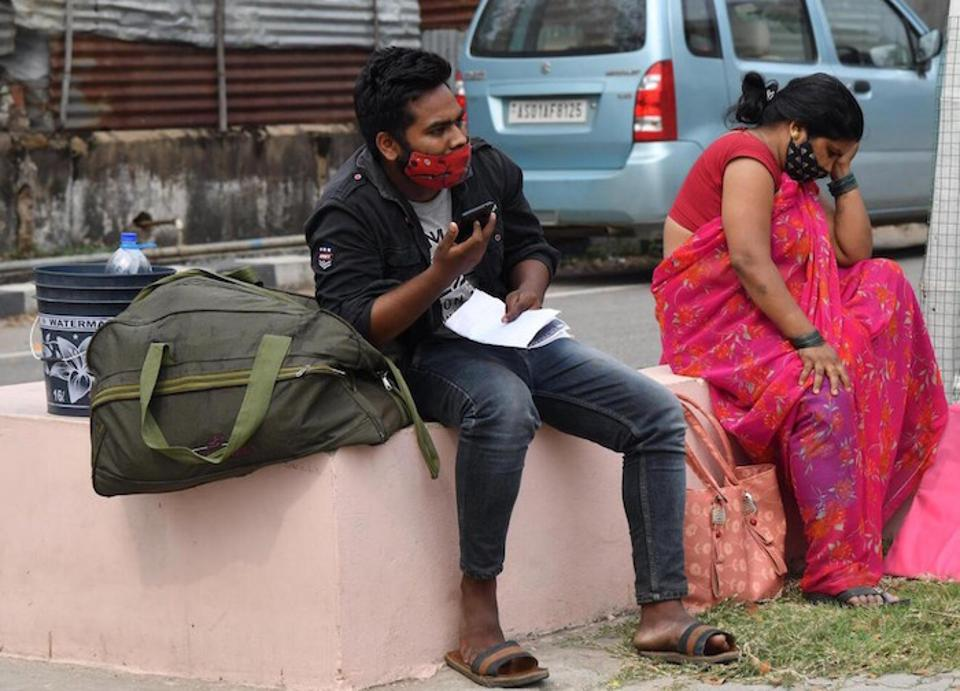 Sitting outside a full COVID care center in Kalapahar, Guwahati, India, a woman in a sari, wearing a mask, rests her head in her hand while next to her a man in a mask holds a cellphone.
