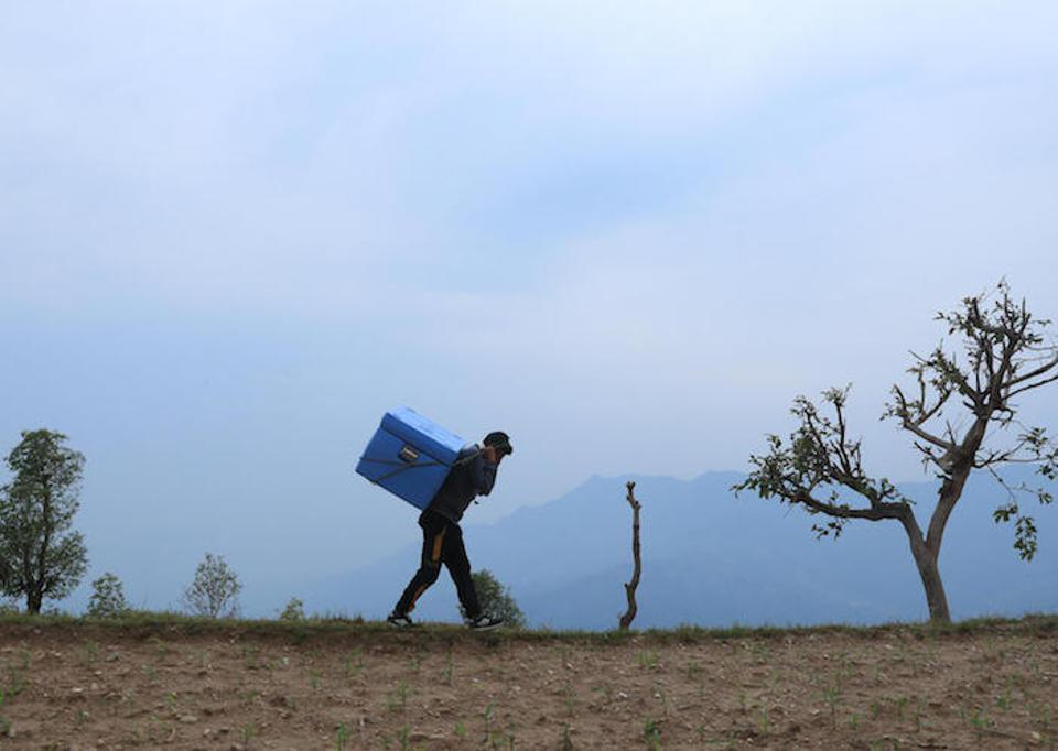 A man carries a large blue container of COVID-19 vaccine doses on his back as he walks across a mountain ridge in rural Nepal.