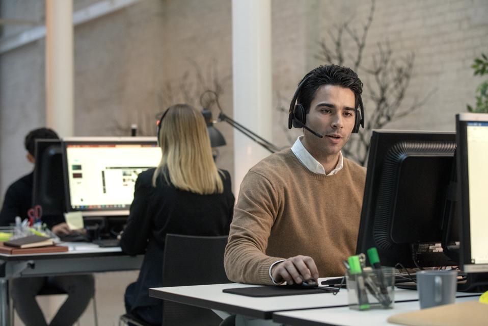 Un hombre en el escritorio usa los auriculares EPOS ADAPT 200