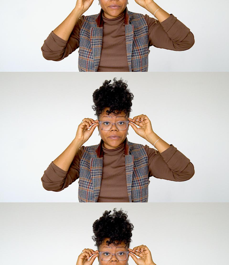 A black woman with glasses wearing a brown turtle neck and plaid vest, standing.