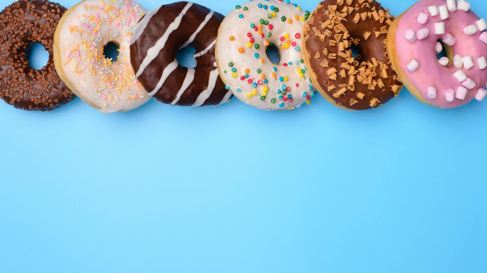 Top above overhead closeup flat lay flatlay view photo of yummy style lot donuts lying in a row isolated over blue pop pastel background